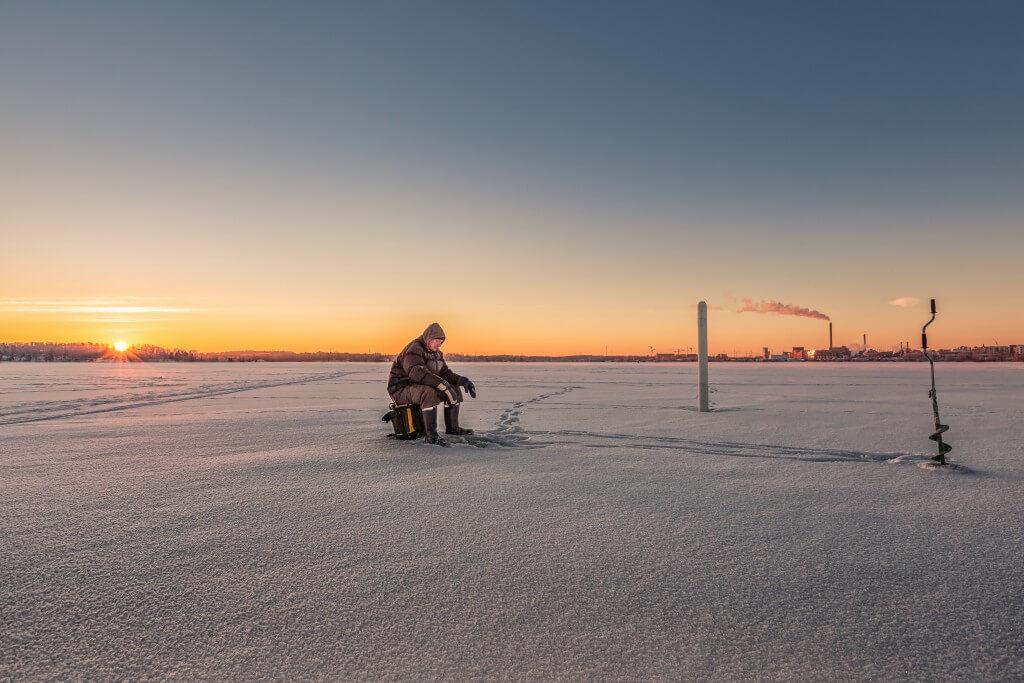 angler im winter auf einer eisfläche mit sonnenaufgang