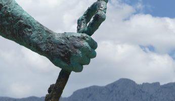 Hand einer Statue mit Wolken im Hintergrund