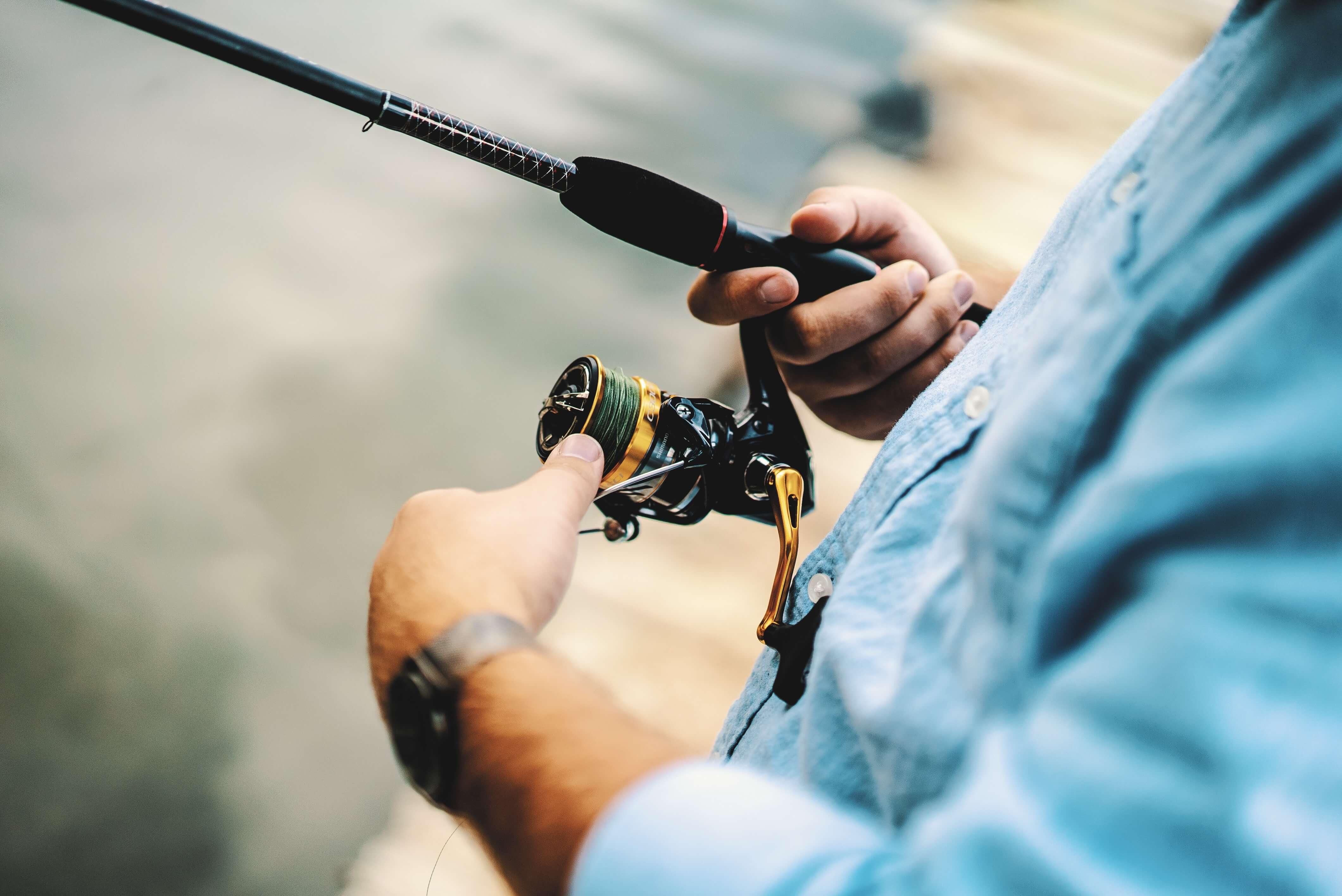Ein Angler hält eine rute in der Hand und dreht an der Spule.