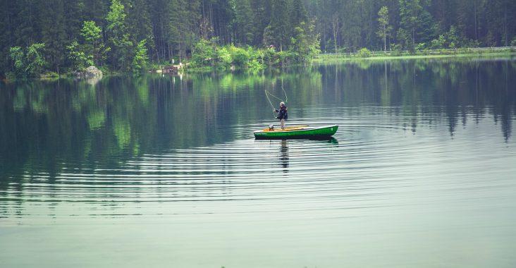 Ein Angler im Boot auf einem See mit Regentimmung.
