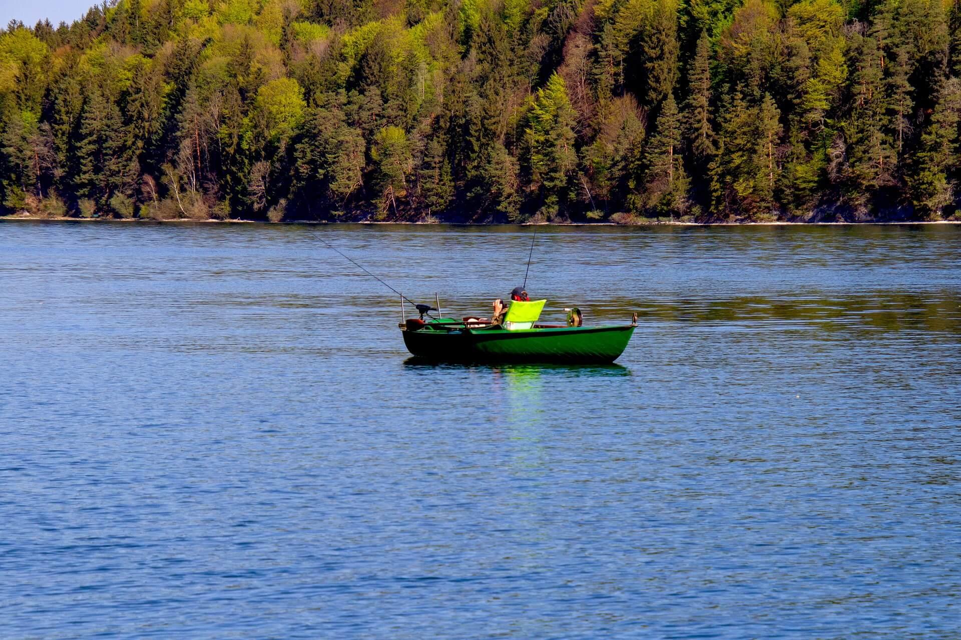 Ein Boot auf einem See mit Angler mit herbstlichen Bäumen im Hintergrund.