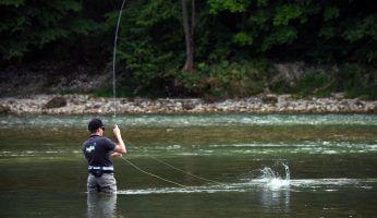 Ein Fliegenfischer mit hejfish Shirt in einem Bach gerade am Fisch fangen.
