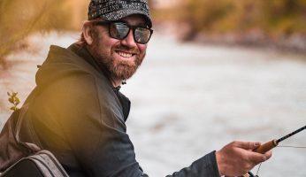 Angler lacht in die Kamera und sitzt an einem Fluss.