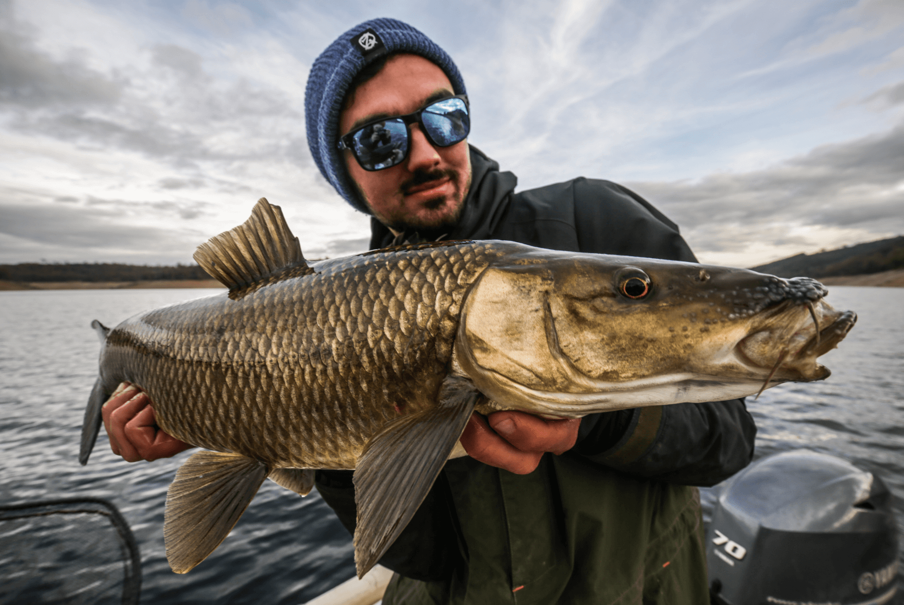 Angler mit einem Fisch in der Hand auf einem Boot.
