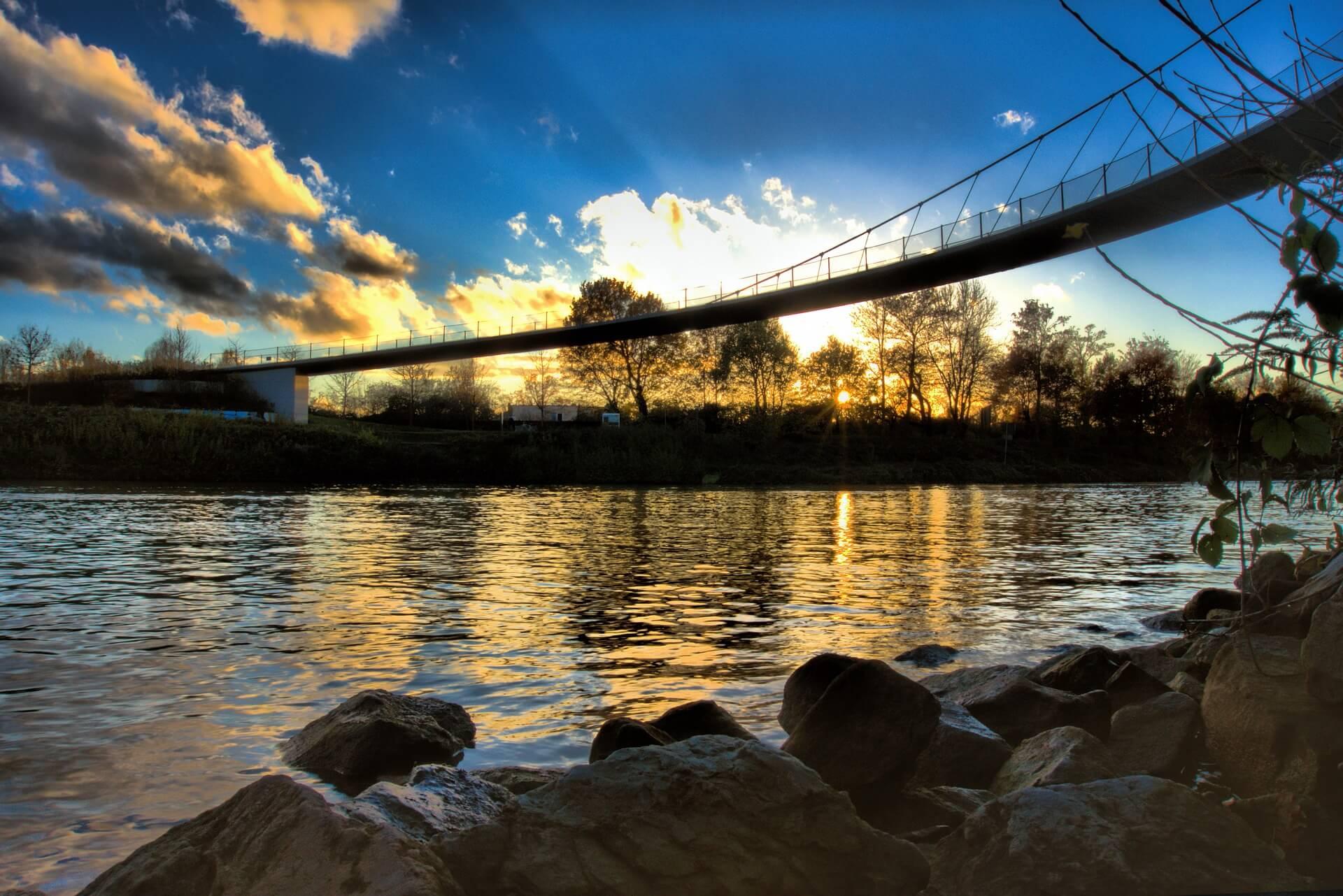 Der Rhein-herne-kanal mit Sonnenuntergang hinter einer Brücke.