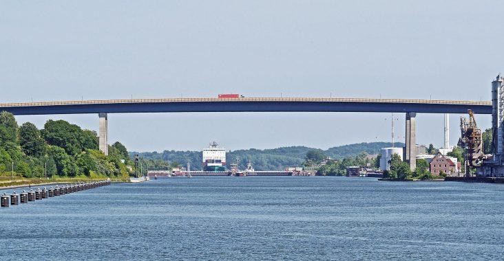Der nord-ostsee-kanal mit einer Brücke an einem wolkenlosen Tag.