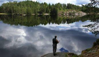 Angler von hinten an einem See.