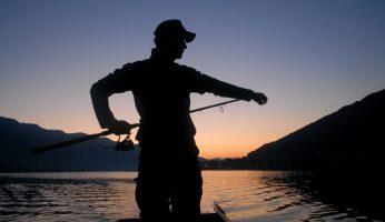 Ein Angler beim angeln mit sonnenuntergang.