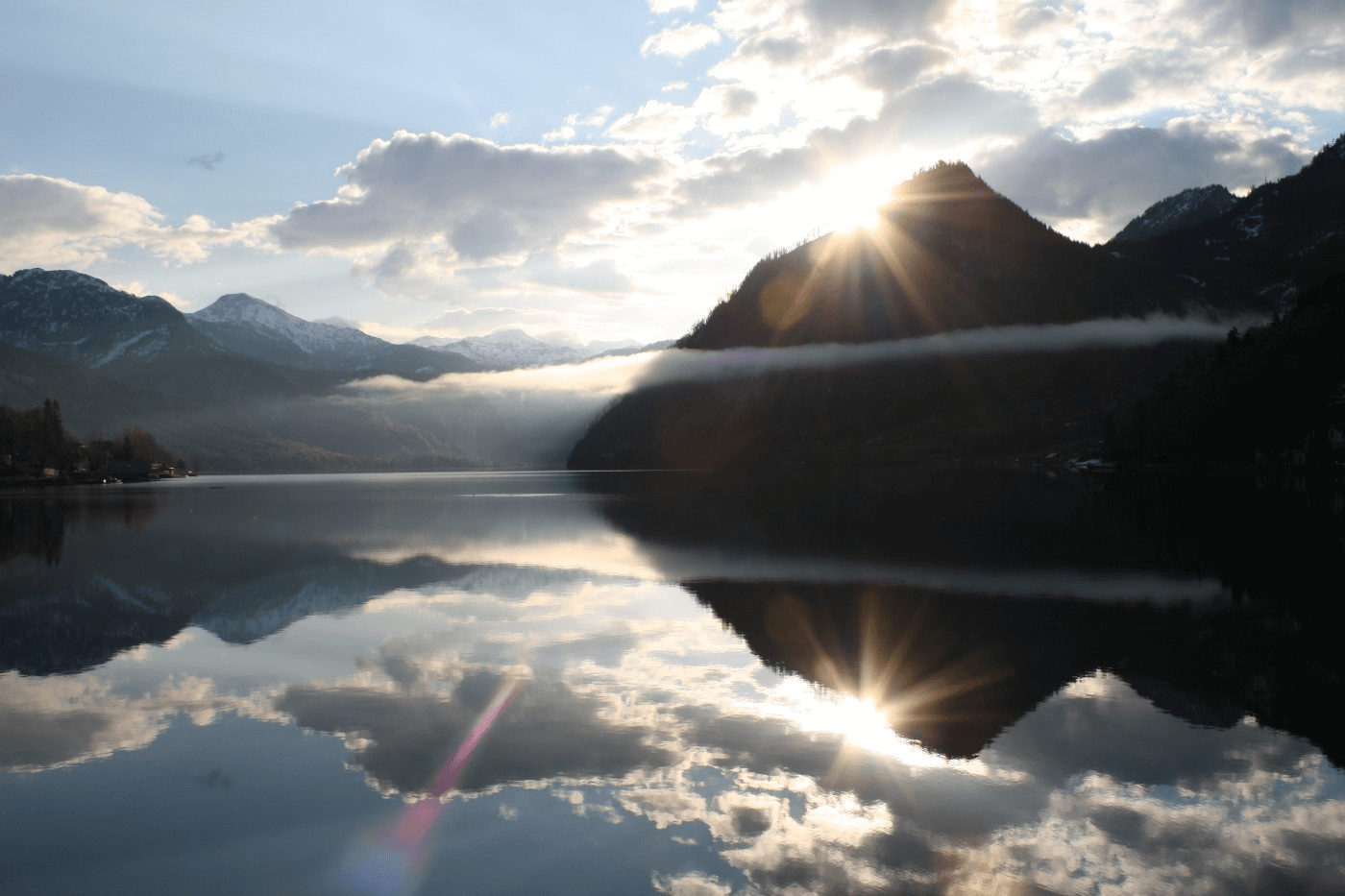 Der Grundlsee mit einer wunderschönen spiegelung der Sonne hinter einem Berg.