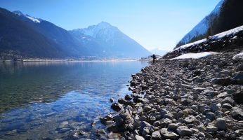 Ein See in den Alpen mit Kiesstrand.