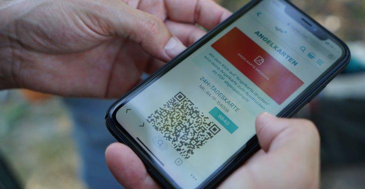 Hände mit Handy worauf man eine Angelkarte erkennt die über hejfish gekauft worden ist.