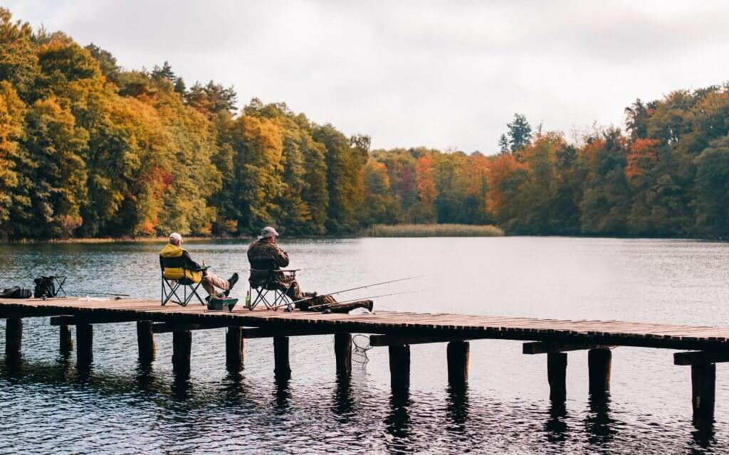 Zwei Angler, die sich zum gemeinsamen Angeln am Wochenende auf einem Steg verabredet haben.