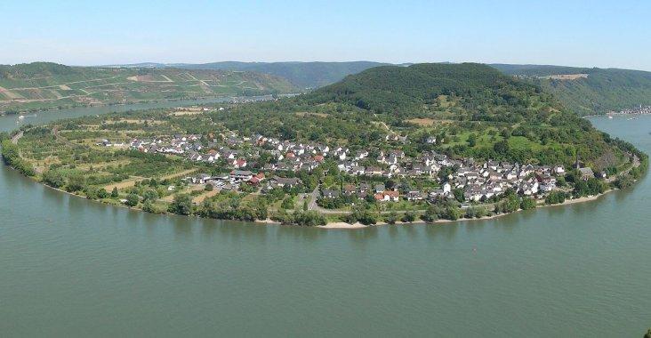 Luftaufnahme vom Rhein mit Dorf und bewaldetem Ufer