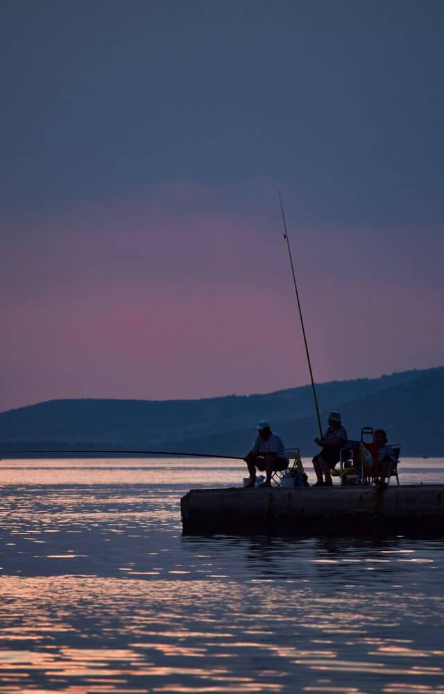 Gemeinsames Angeln am See bei Sonnenuntergang Angelverein