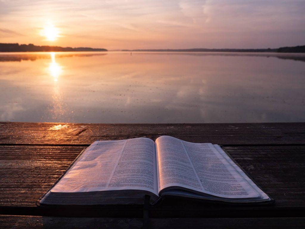 Buch lesen am See bei Sonnenuntergang