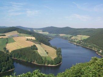 Der Diemelsee inmitten von Hügeln mit Feldern an einem Tag mit blauem Himmel.