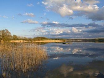 Der Dobersdorfer see im Abendlicht mit Spiegelung der Wolken im Wasser.