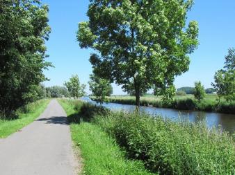 hadelner kanal mit Radweg und Bäumen an einem Schönwetter Tag.